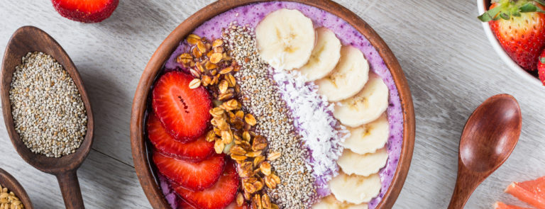 A pink acai bowl topped with bananas, various seeds and strawberries. Half a pink grapefruit on a table with dried fruit and strawberries around the acai bowl.