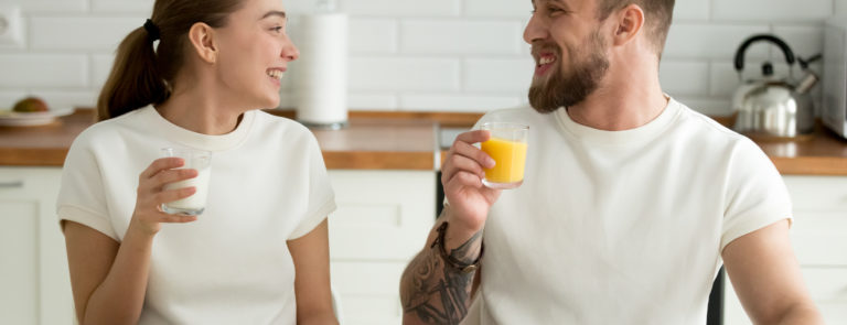 A man and woman looking at eachother smiling and drinking orange juice, with salad on the table.