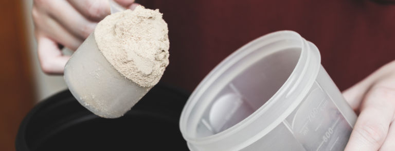 A hand pouring a scoop of casein into a protein cup.