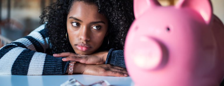 A lady looking at a piggy bank with a note and some coins on the table.