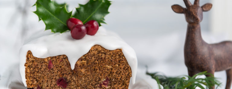 A vegan Christmas pudding topped with holly and berries. With a stag statue behind.