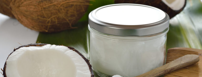 Half of a coconut with a jar of coconut oil and a spoon with coconut oil on.