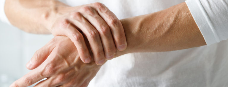 Close up of male arms holding a painful wrist