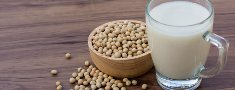 Soy beans in a bowl next to a glass of soya milk.