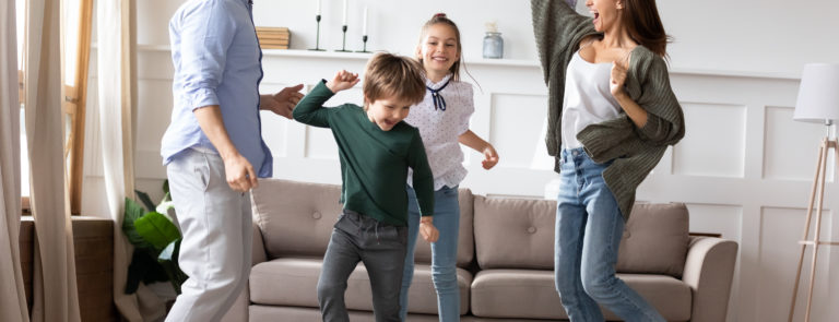 family energetically dancing around room