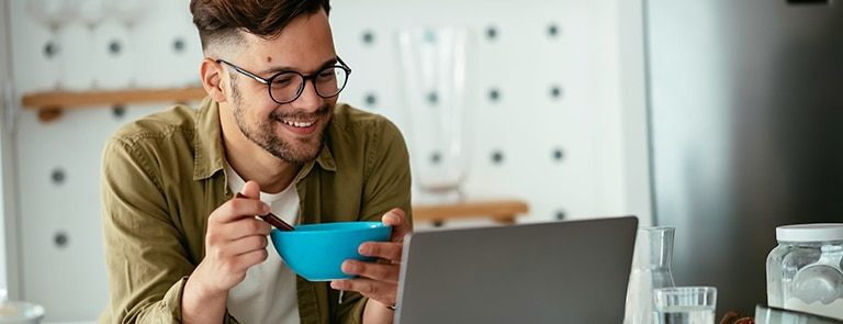 A man eating cereal whilst watching his laptop.