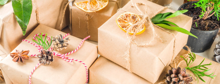 A selection of presents wrapped in brown paper with both red and white and beige string around them and decorated with pine cones, leaves and dried orange slices.