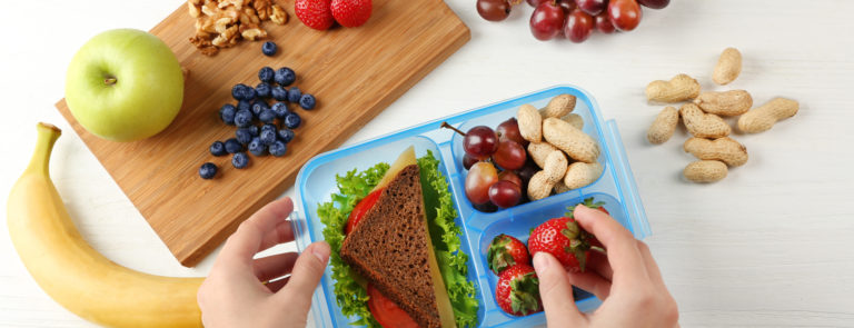 A lunch box with a sandwich and variety of fruits and nuts included. As well as a chopping board with nuts, blueberries, strawberries and grapes around it.