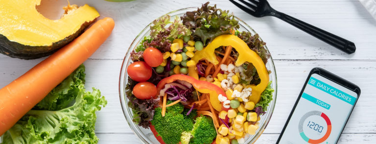 A salad bowl surrounded by vegetables and a phone calorie app open.