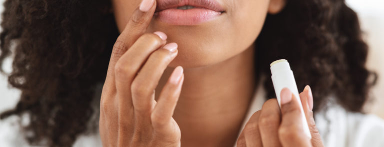 A lady applying lip balm to her lips.