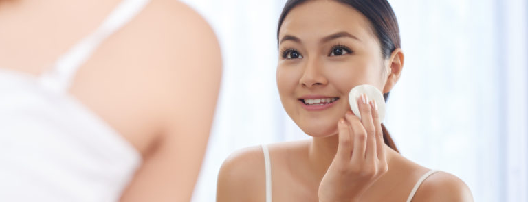 A woman looking in a mirror with a cotton pad, using toner on her face.