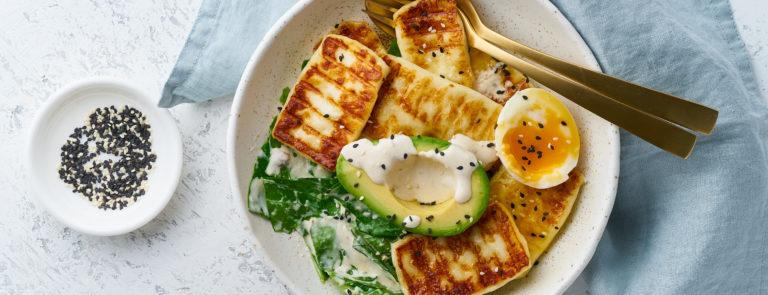 A bowl with half an avocado, brocolli, half a boiled egg and tofu.