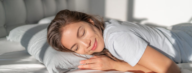 A lady sleeping in bed and smiling.