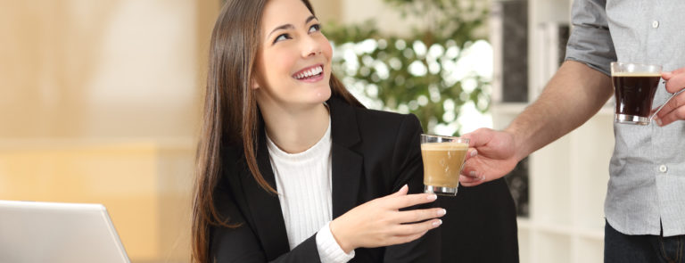 A lady receiving a latte from a work colleague.