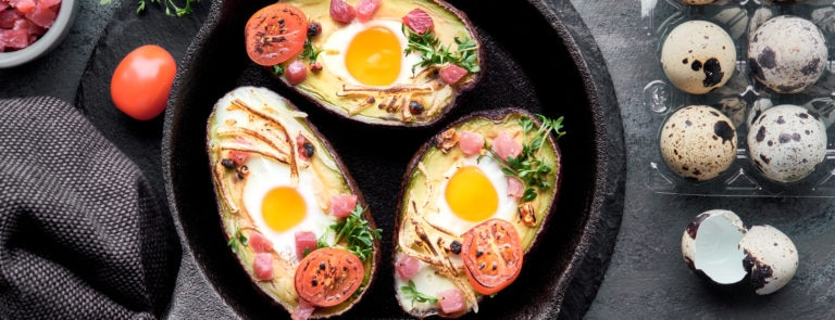 Three Avocado boats with fried eggs and tomatoes inside.