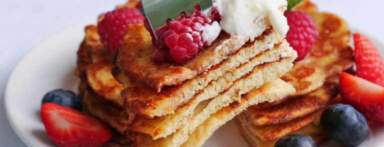 A stack of 5 keto pancakes topped with strawberries, cream and a fork in the top.