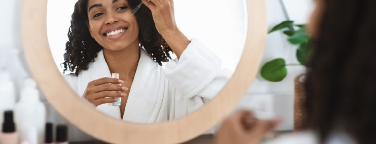 a young woman smiling in the mirror and applying skin serum to her face